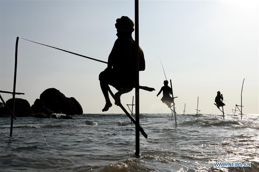 Stilt fishermen are silhouetted at a beach in Galle, Sri Lanka, April 7, 2019. Stilt fishing is a method of fishing unique to the island country of Sri Lanka. Local fishermen sit on a crossbar called \