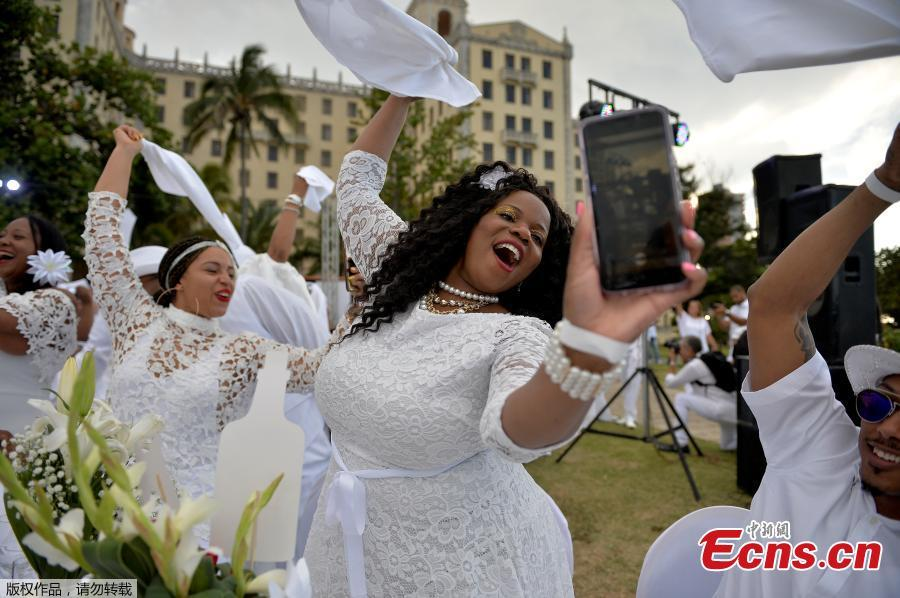 Guests in white costumes pose for a selfie during the \'Diner en Blanc\' event, at the Hotel Nacional in Havana on April 6, 2019. Around 500 people from different countries took part in the event. (Photo/Agencies)