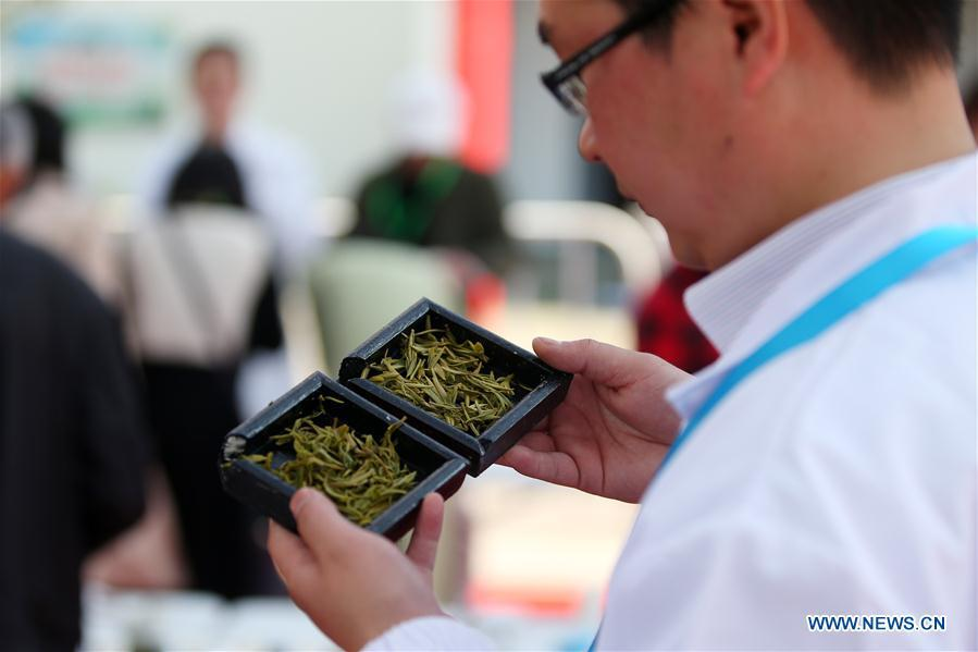 An expert examines used tea leaves during a tea competition in Huangshan, a famous tea producing area in east China\'s Anhui Province, April 7, 2019. Local tea farmers bring a total of 60 varieties of tea leaves to take part in the competition here on Sunday. (Xinhua/Shi Yalei)