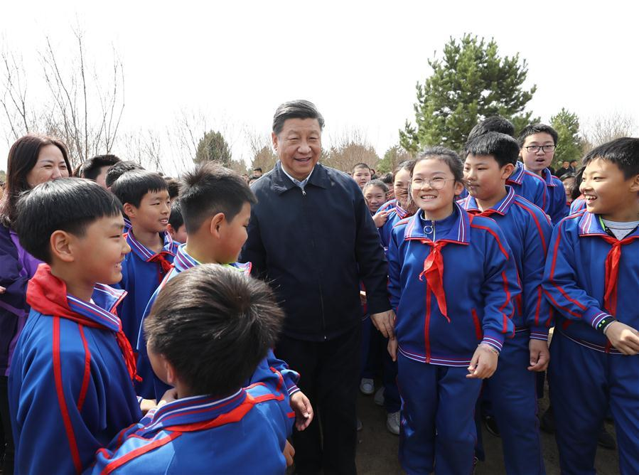 Chinese President Xi Jinping, also general secretary of the Communist Party of China Central Committee and chairman of the Central Military Commission, talks with school children as he attends a tree-planting activity in Tongzhou District in Beijing, capital of China, April 8, 2019. Other Party and state leaders, including Li Zhanshu, Wang Yang, Wang Huning, Zhao Leji, Han Zheng and Wang Qishan, also attended the activity. (Xinhua/Ju Peng)