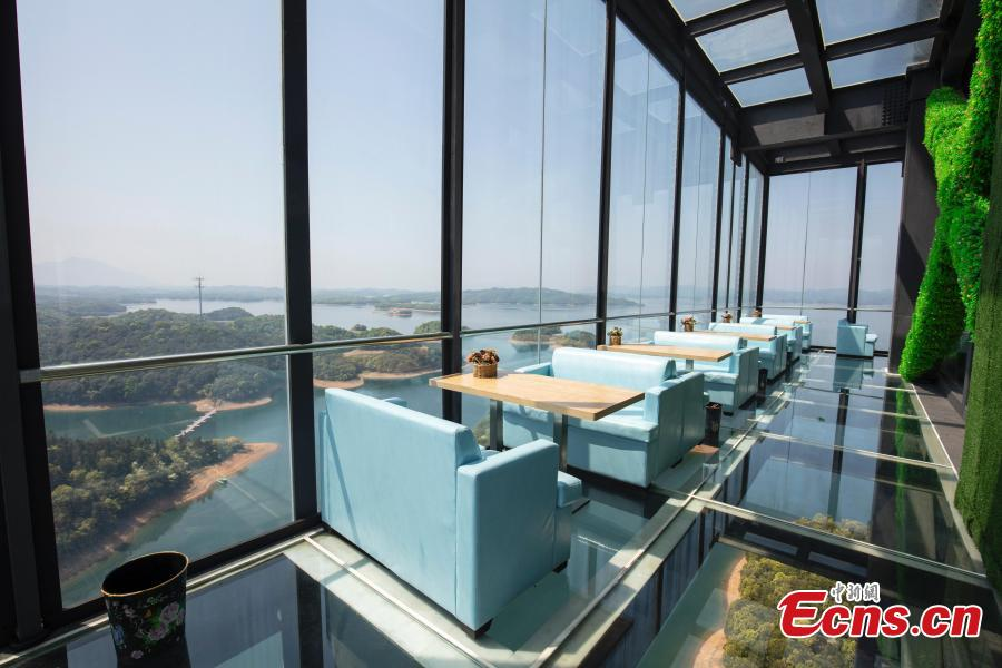 A view of a café inside a glass sightseeing tower, 99 meters above the ground, in Lushan Xihai scenic area in Yongxiu County, East China\'s Jiangxi Province, April 7, 2019. Visitors to the tower can enjoy great views of the mountain and lake. (Photo: China News Service/Zhang Haiyan)