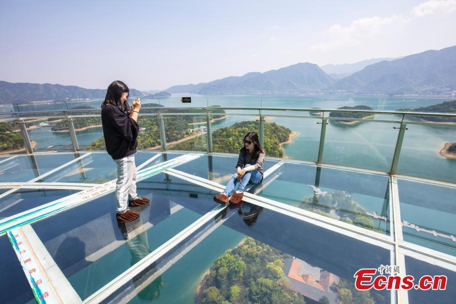 Tourists take photos on the platform of a glass sightseeing tower, 99 meters above the ground, in Lushan Xihai scenic area in Yongxiu County, East China\'s Jiangxi Province, April 7, 2019. Visitors to the tower can enjoy great views of the mountain and lake. (Photo: China News Service/Zhang Haiyan)