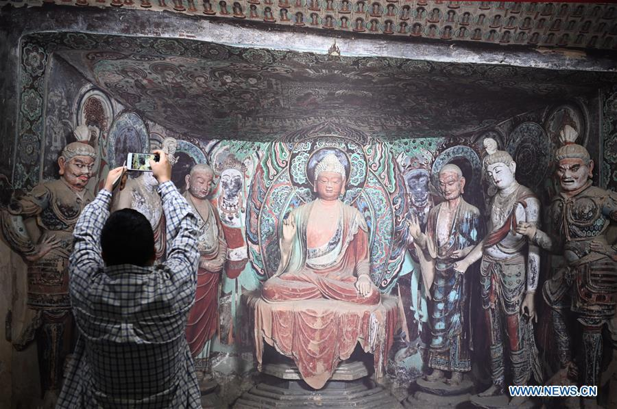 A visitor takes photos of a fresco during a Dunhuang fresco itinerant exhibition in Yunnan University in Kunming, southwest China\'s Yunnan Province, April 10, 2019. A Dunhuang fresco itinerant exhibition, with the participation of nearly 50 frescoes, was held in Yunnan University in Kunming Wednesday. (Xinhua/Qin Qing)