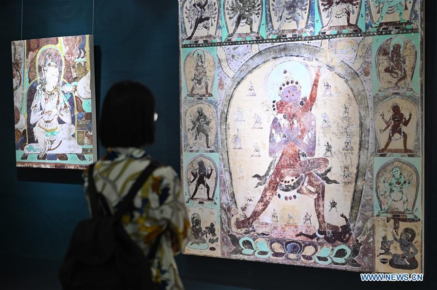 A visitor views frescoes during a Dunhuang fresco itinerant exhibition in Yunnan University in Kunming, southwest China\'s Yunnan Province, April 10, 2019. A Dunhuang fresco itinerant exhibition, with the participation of nearly 50 frescoes, was held in Yunnan University in Kunming Wednesday. (Xinhua/Qin Qing)
