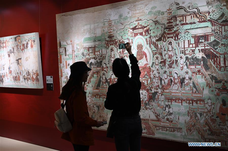 Visitors view a fresco during a Dunhuang fresco itinerant exhibition in Yunnan University in Kunming, southwest China\'s Yunnan Province, April 10, 2019. A Dunhuang fresco itinerant exhibition, with the participation of nearly 50 frescoes, was held in Yunnan University in Kunming Wednesday. (Xinhua/Qin Qing)