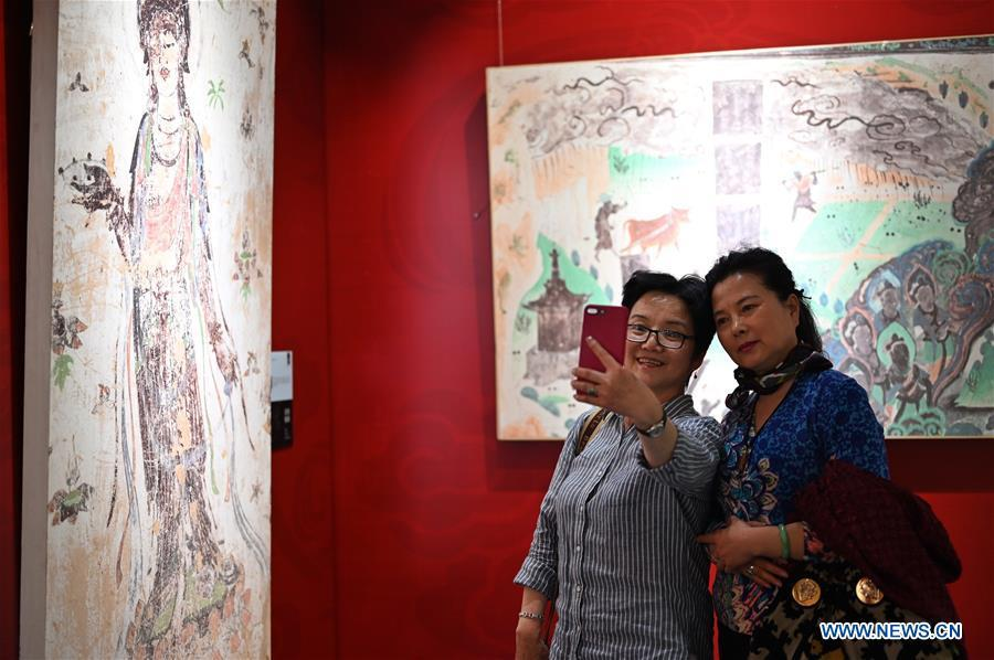 Visitors pose for a group photo during a Dunhuang fresco itinerant exhibition in Yunnan University in Kunming, southwest China\'s Yunnan Province, April 10, 2019. A Dunhuang fresco itinerant exhibition, with the participation of nearly 50 frescoes, was held in Yunnan University in Kunming Wednesday. (Xinhua/Qin Qing)