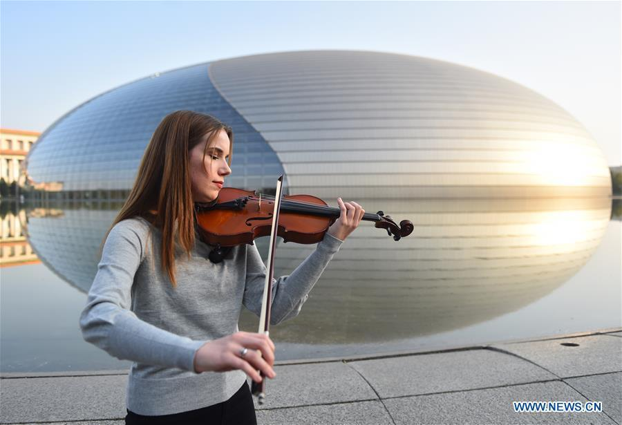 Aleksandra Denga, from Poland, improvises as she poses for a photo in front of the National Centre for the Performing Arts in Beijing, capital of China, Oct. 19, 2018. After her graduation from Academy of Music in Gdansk in 2014, Aleksandra came to China to work with Guiyang Symphony Orchestra as a violinist in southwest China\'s Guizhou Province, three years later after a short stay in Poland, she decided to come back to China again, this time she found a job in National Centre for the Performing Arts Orchestra. \
