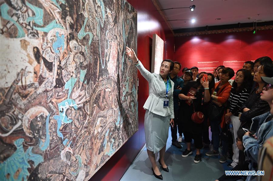 Ma Lin(L), a guide from Dunhuang Academy China, explains fresco culture to visitors during a Dunhuang fresco itinerant exhibition in Yunnan University in Kunming, southwest China\'s Yunnan Province, April 10, 2019. A Dunhuang fresco itinerant exhibition, with the participation of nearly 50 frescoes, was held in Yunnan University in Kunming Wednesday. (Xinhua/Qin Qing)