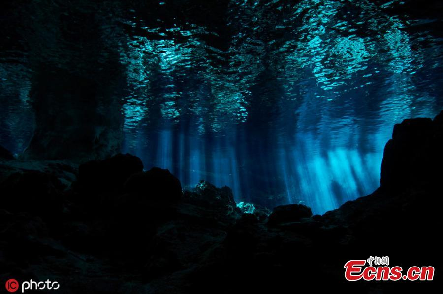 Photo taken by Kirk Zhang shows people diving in freshwater in cenotes illuminated with sunlight from the outside in Mexico. Diving in the caverns, windows to large underground river systems, is a unique experience with  amazing light effects. (Photo/IC)