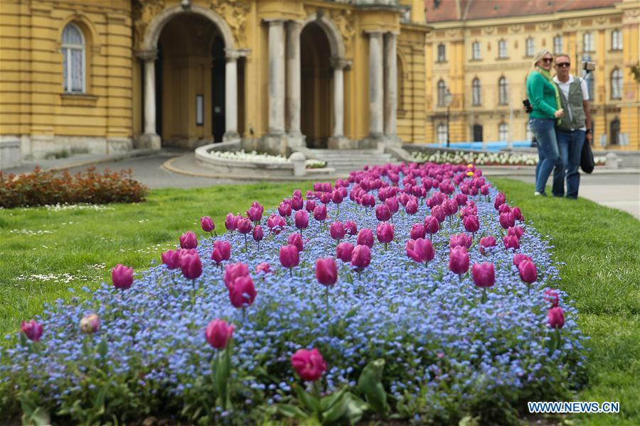 Photo taken on April 10, 2019 shows tourists taking photos with flowers outside the Croatian National Theatre in downtown Zagreb, capital of Croatia. (Xinhua/Zheng Huansong)