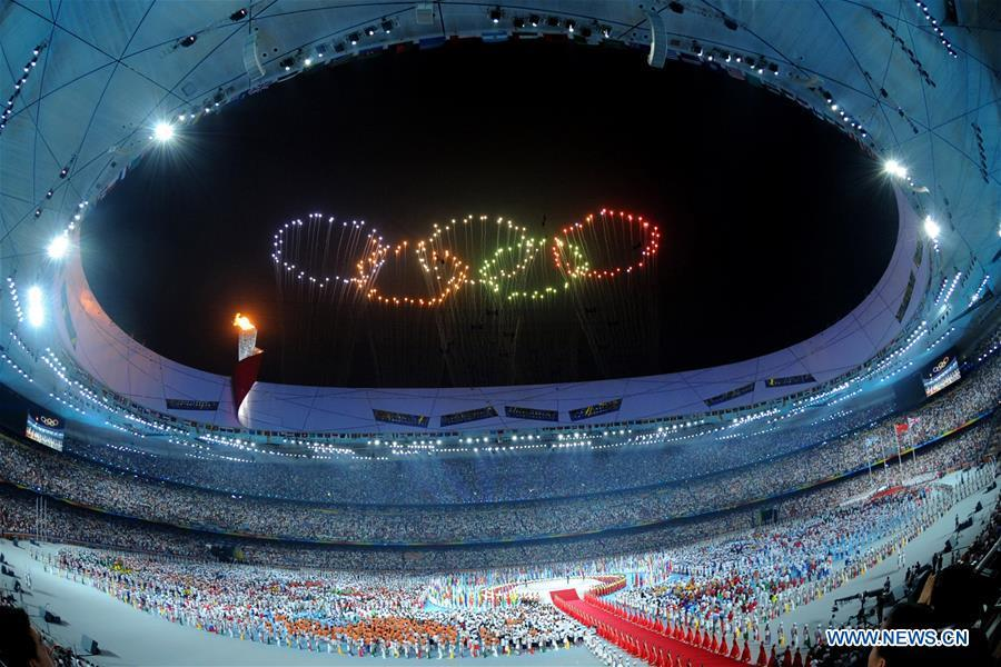 Photo taken on Aug. 8, 2008 shows the fireworks in the shape of Olympic rings during the opening ceremony of the Beijing Olympic Games held in the National Stadium, also known as the Bird\'s Nest, in north Beijing, China. From sending athletes to Helsinki Summer Olympic Games for the very first time in 1952 to winning the bid to host 2022 Winter Olympic Games in 2015, the People\'s Republic of China went through a remarkable history of sports, including successfully hosting the 2008 Summer Olympic Games and preparing for the upcoming 2022 Winter Olympic Games. (Xinhua/Ma Zhancheng)