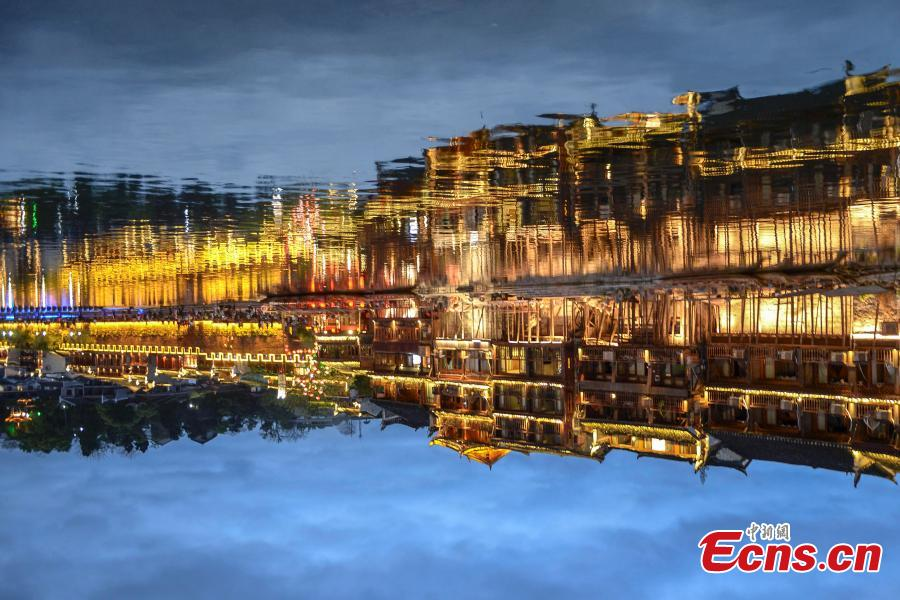 Illuminated buildings are reflected in the Tuojiang River in Fenghuang Ancient Town, Hunan Province, April 11, 2019. The old town is famous for its time-honored buildings and cultural relics, attracting large numbers of visitors each year from China and abroad. (Photo: China News Service/Yang Huafeng)