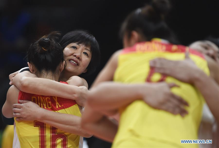 File photo taken on August 20, 2016 shows that Lang Ping (2nd L), head coach of China\'s team, hugs teammate Ding Xia during the women\'s gold medal match of Volleyball at the 2016 Rio Olympic Games in Rio de Janeiro, Brazil. From sending athletes to Helsinki Summer Olympic Games for the very first time in 1952 to winning the bid to host 2022 Winter Olympic Games in 2015, the People\'s Republic of China went through a remarkable history of sports, including successfully hosting the 2008 Summer Olympic Games and preparing for the upcoming 2022 Winter Olympic Games. (Xinhua/Li Ga)