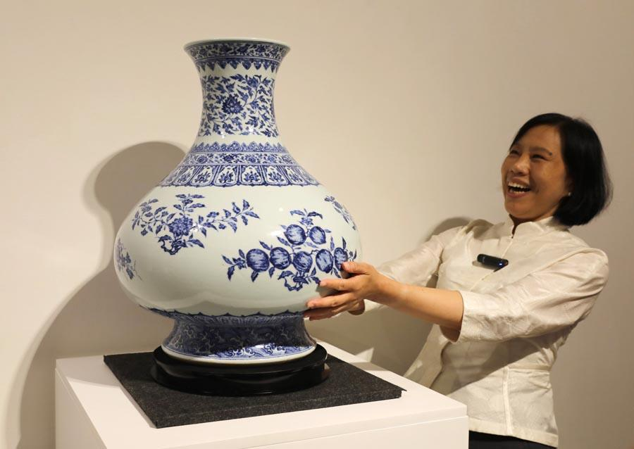 A staff member introduces a Qing Dynasty porcelain vessel created during the reign of Emperor Yongzheng at a media preview of Christie\'s Hong Kong Spring Auctions, April 11, 2019. (Photo/Xinhua)