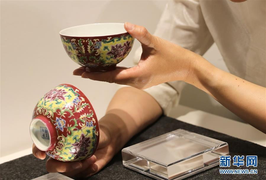 A staff member of auction house Christie\'s shows a pair of Qing Dynasty (1644-1911) porcelain bowls created during the reign of Emperor Yongzheng (1678-1735), at a media preview on April 11, 2019. The Christie\'s Hong Kong Spring Auctions 2019 will be held in Hong Kong from May 24 to 29. Those to go under the hammer include several treasured porcelain and handcraft works from ancient China, each estimated at more than HK$10 million ($1.2 million). (Photo/Xinhua)