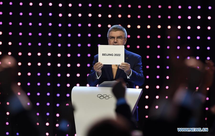 File photo taken on July 31, 2015 shows International Olympic Committee (IOC) president Thomas Bach shows the card with the name Beijing as the winning name of the 2022 Winter Olympic bid city, during the 128th International Olympic Committee (IOC) session in Kuala Lumpur, Malaysia. From sending athletes to Helsinki Summer Olympic Games for the very first time in 1952 to winning the bid to host 2022 Winter Olympic Games in 2015, the People\'s Republic of China went through a remarkable history of sports, including successfully hosting the 2008 Summer Olympic Games and preparing for the upcoming 2022 Winter Olympic Games. (Xinhua/Gong Lei)