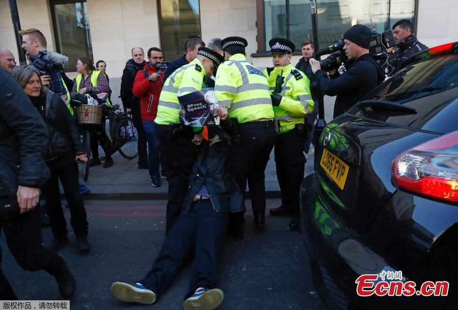 A demonstrator is carried away by police officers after trying to stop a vehicle as it leaves Westminster magistrates court where WikiLeaks founder Julian Assange was appearing in London, April 11, 2019.(Photo/Agencies)