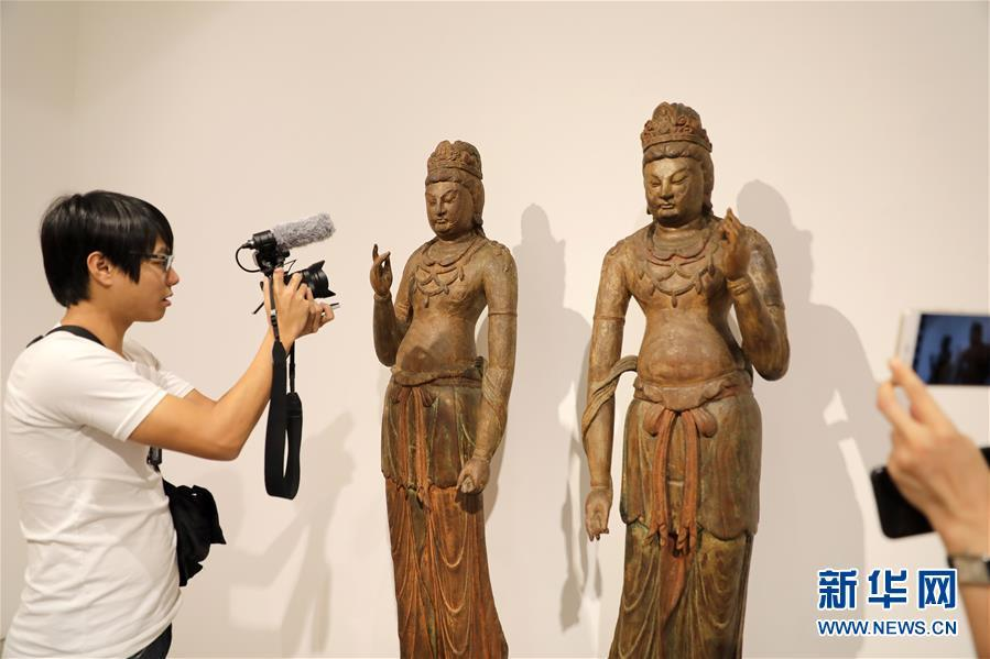 A journalist takes photos of two woodcarving Bodhisattva statues from ancient China\'s Five Dynasties to North Song Dynasty (907-1127) at a media preview of Christie\'s Hong Kong Spring Auctions, April 11, 2019. The estimated price is HK$32 million to HK$45 million ($4-$6 million).  (Photo/Xinhua)