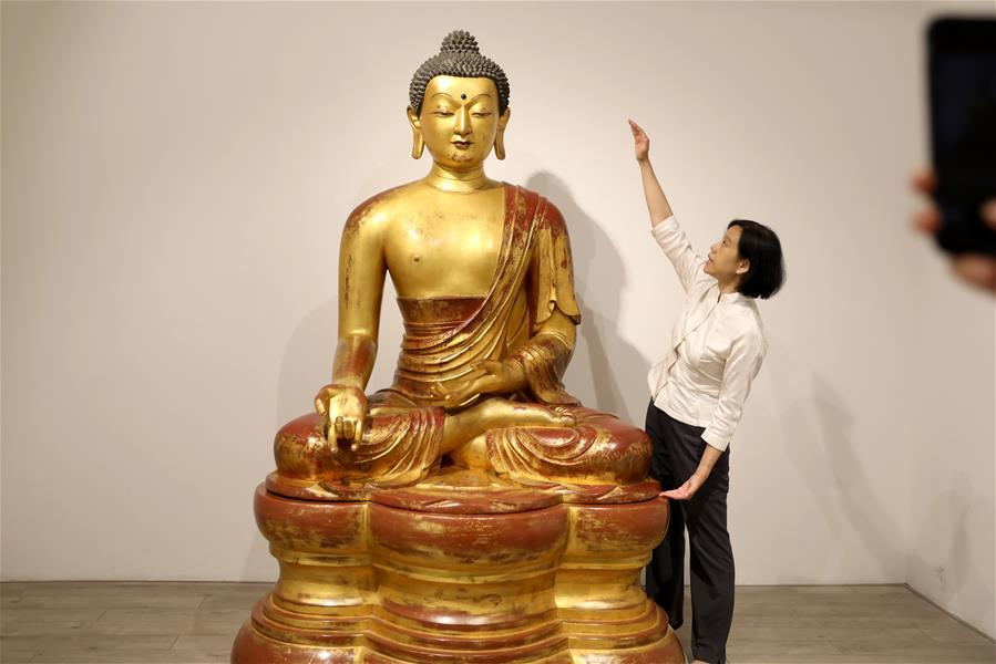 A staff member introduces a Qing Dynasty Buddha statue at a media preview of Christie\'s Hong Kong Spring Auctions, April 11, 2019. The estimated price of the 1.72-meter-tall statue is HK$30 million to HK$50 million ($4-$6 million).  (Photo/Xinhua)