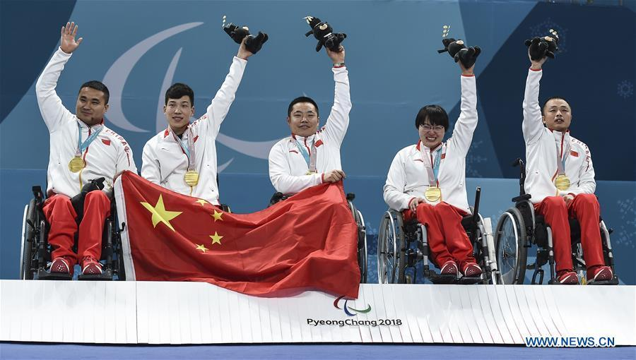 File photo taken on March 17, 2018 shows gold medalists, China\'s Wang Haitao, Chen Jianxin, Liu Wei, Wang Meng and Zhang Qiang (L to R) celebrating on the podium during the awarding ceremony for wheelchair curling at the 2018 PyeongChang Winter Paralympic Games at Gangneung, South Korea. China beat Norway in the final 6-5 to claim the title of the event, which is also China\'s first-ever Winter Paralympic medal with gold. From sending athletes to Helsinki Summer Olympic Games for the very first time in 1952 to winning the bid to host 2022 Winter Olympic Games in 2015, the People\'s Republic of China went through a remarkable history of sports, including successfully hosting the 2008 Summer Olympic Games and preparing for the upcoming 2022 Winter Olympic Games. (Xinhua/Xia Yifang)