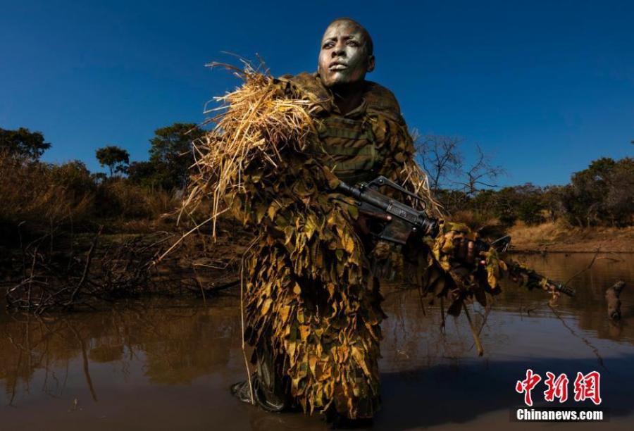 Environment, singles winner  Petronella Chigumbura, an elite member of the all-female conservation ranger force known as Akashinga that operates in Zimbabwe\'s Lower Zambezi, undergoes sniper movement and concealment training in the bush near their base.   Photograph: Brent Stirton/Getty Images