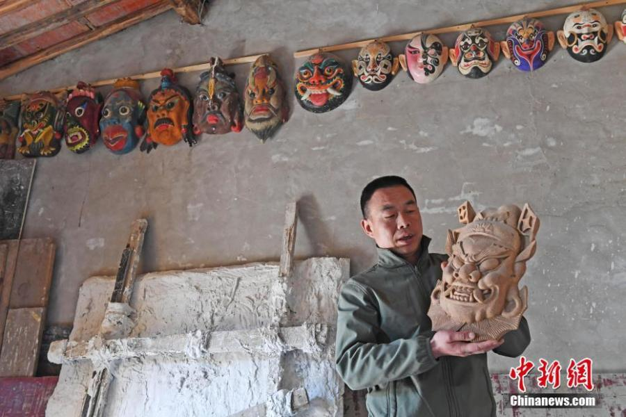 Ma Lande shows masks of the Nuo Opera at his studio in Lanzhou City, Northwest China\'s Gansu Province, April 14, 2019. The handicraftsman said he has made more than 2,000 Nuo Opera masks in the past 17 years, depicting a broad range of topics, including mythical figures from Chinese legends and classic novels. Masks, usually carved out of willow or camphor wood, are an important part of Nuo Opera, an ancient folk drama still popular in some parts of China. The purpose of Nuo Opera is to drive away devils, disease and evil influences, and also to petition the gods for their blessings. (Photo: China News Service/Yang Yanmin)