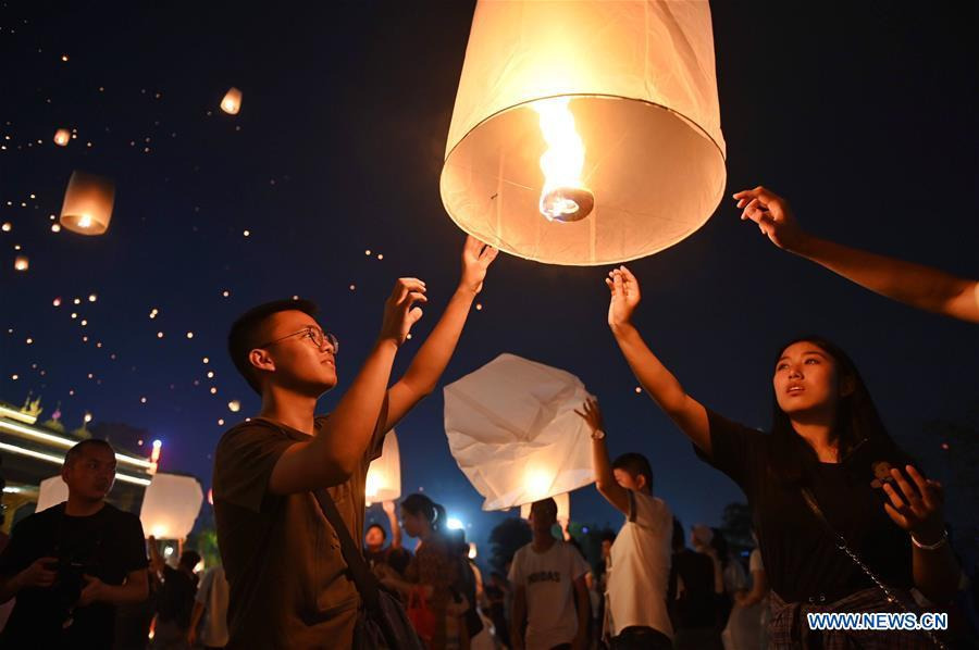 People fly Kongming lanterns, a kind of small hot-air paper balloon, by the Lancang River in Jinghong City, southwest China\'s Yunnan Province, April 13, 2019, to celebrate the New Year of the calendar of the Dai ethnic group. (Xinhua/Qin Qing)