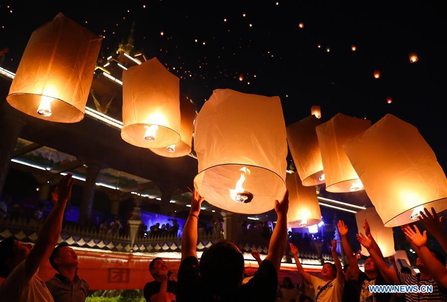 People fly Kongming lanterns, a kind of small hot-air paper balloon, by the Lancang River in Jinghong City, southwest China\'s Yunnan Province, April 13, 2019, to celebrate the New Year of the calendar of the Dai ethnic group. (Xinhua/Zhang Yuwei)