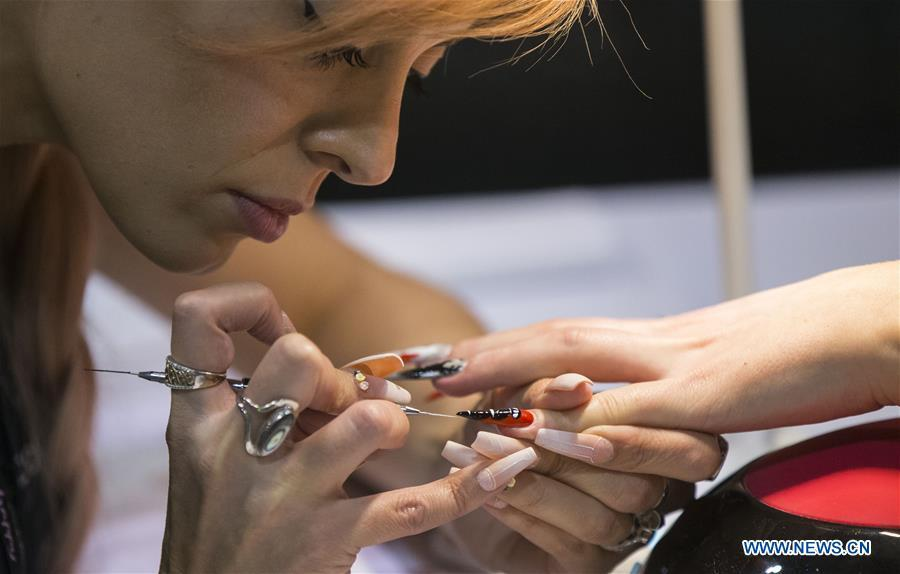A competitor works on nail painting during the Nail Art Challenge at the 2019 Revel in Beauty event in Toronto, Canada, on April 15, 2019. The Nail Art Challenge was held on Monday to showcase the creative process of nail art to spectators. (Xinhua/Zou Zheng)
