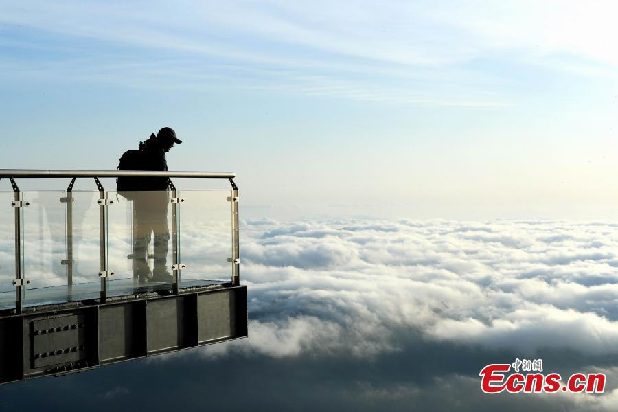 A photographer looks at clouds surrounding Mount Sanqing in Jiangxi Province. (Photo: China News Service/Zhang Hezhong)