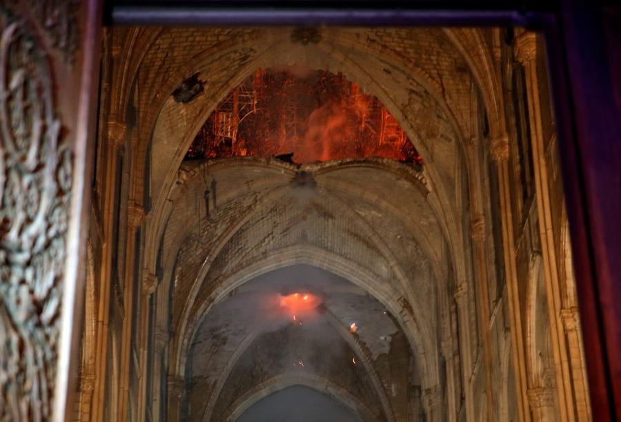 Photo shows the burning roof of Notre-Dame inside the cathedral.  A blaze broke out on Monday afternoon at the Notre Dame Cathedral in central Paris. (Photo/Agencies)