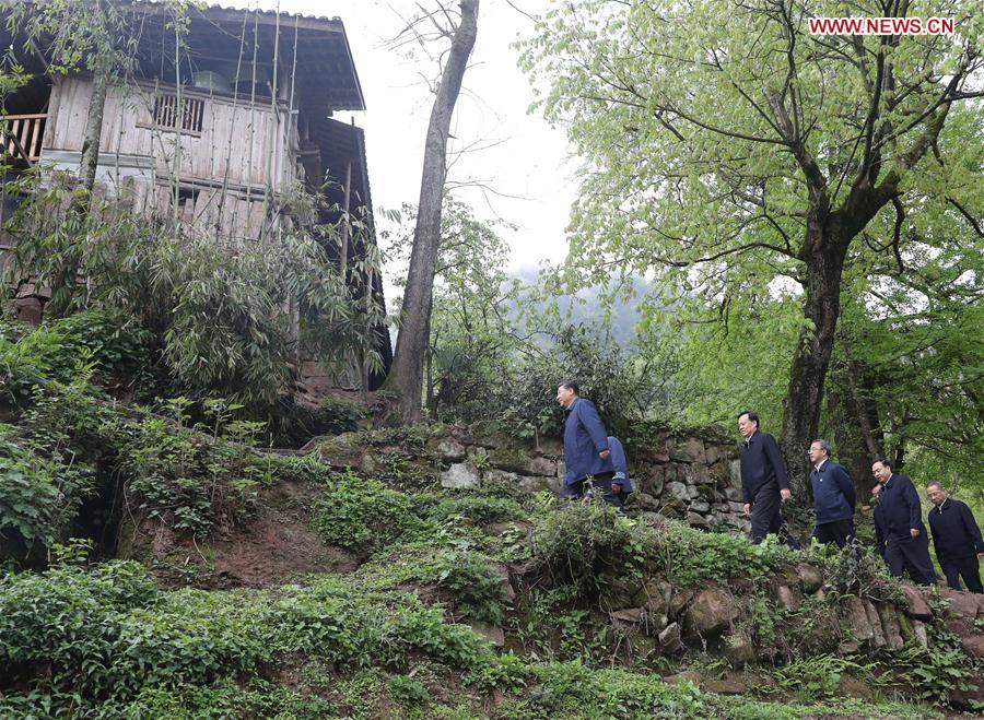 Chinese President Xi Jinping, also general secretary of the Communist Party of China Central Committee and chairman of the Central Military Commission, walks to a villager\'s home to learn about the progress of poverty alleviation and in solving prominent problems including meeting the basic need of food and clothing and guaranteeing compulsory education, basic medical care and safe housing, in Huaxi Village of Shizhu Tujia Autonomous County, southwest China\'s Chongqing, April 15, 2019. Xi went on an inspection tour in southwest China\'s Chongqing Municipality Monday. (Xinhua/Wang Ye)