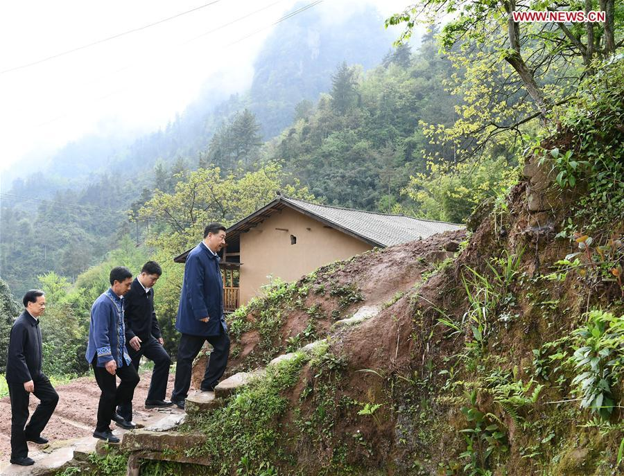Chinese President Xi Jinping, also general secretary of the Communist Party of China Central Committee and chairman of the Central Military Commission, walks to a villager\'s home to learn about the progress of poverty alleviation and in solving prominent problems including meeting the basic need of food and clothing and guaranteeing compulsory education, basic medical care and safe housing, in Huaxi Village of Shizhu Tujia Autonomous County, southwest China\'s Chongqing, April 15, 2019. Xi went on an inspection tour in southwest China\'s Chongqing Municipality Monday. (Xinhua/Xie Huanchi)