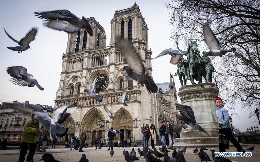 In this file photo taken on March 13, 2015, tourists visit the Notre Dame Cathedral in Paris, France. The devastating fire at Notre Dame Cathedral in central Paris has been put out after burning for 15 hours, local media reported on April 16, 2019. In early evening on April 15, a fire broke out in the famed cathedral. Online footage showed thick smoke billowing from the top of the cathedral and huge flames between its two bell towers engulfing the spire and the entire roof which both collapsed later. Notre Dame is considered one of the finest examples of French Gothic architecture which receives about 12 million visitors every year. (Xinhua/Chen Xiaowei)