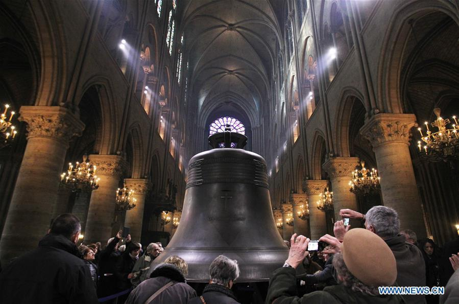 In this file photo taken on Feb. 15, 2013, visitors look at a new bronze bell made to celebrate the 850th anniversary of the Notre Dame Cathedral in Paris, France. The devastating fire at Notre Dame Cathedral in central Paris has been put out after burning for 15 hours, local media reported on April 16, 2019. In early evening on April 15, a fire broke out in the famed cathedral. Online footage showed thick smoke billowing from the top of the cathedral and huge flames between its two bell towers engulfing the spire and the entire roof which both collapsed later. Notre Dame is considered one of the finest examples of French Gothic architecture which receives about 12 million visitors every year. (Xinhua/Gao Jing)
