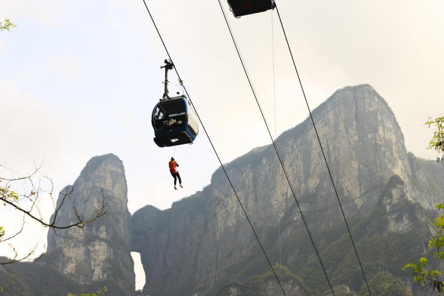 A rescue worker travels along the ropeway to a \