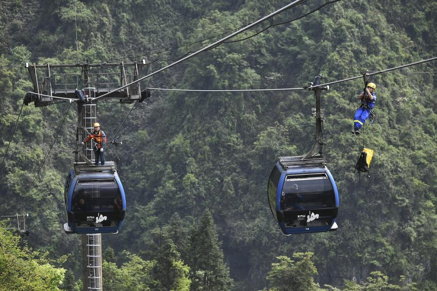 Rescue workers ride the ropeway to \