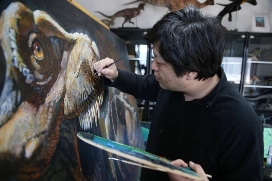 Zhao Chuang works on a dinosaur-themed painting in Shunyi district, Beijing. (Photo/China Daily)