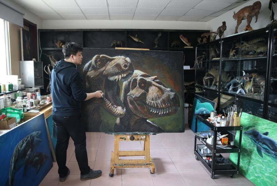 Zhao Chuang with his dinosaur-themed painting. (Photo/China Daily)
