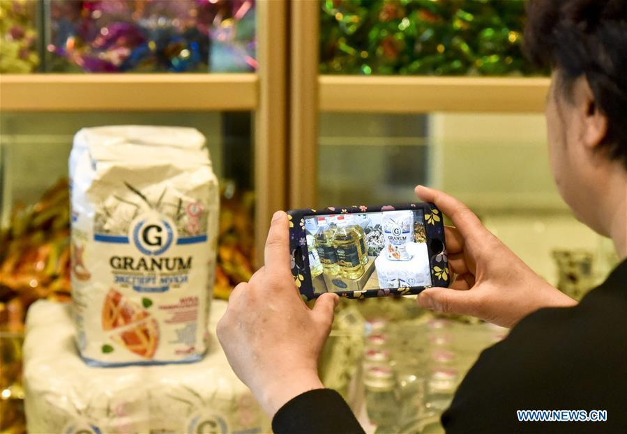 A food vender takes photos of oil and flour imported from Kazakhstan at a store for imported food in Urumqi, northwest China\'s Xinjiang Uygur Autonomous Region, April 12, 2017. Food of a particular place is an important symbol of local geographic and cultural characteristics. Food carries history and tradition, leads the tide of trade, strengthens diplomatic relations, disseminates and promotes culture. Food has been serving as connections between people around the world. In ancient times, food such as grapes, pomegranates, walnuts, coriander, cucumbers and sesame seeds were introduced to China along the Silk Road. Nowadays, thanks to the Belt and Road Initiative, red wine, coffee, dried fruits, meat, seafood, and dairy products from foreign countries enter the homes of ordinary people, turning daily meals into feasts with exotic cuisines. (Xinhua/Hu Huhu)