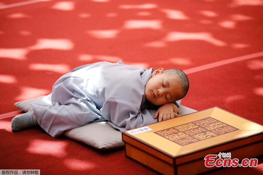 A boy sleeps on the ground after having his head shaved during the \'Children becoming Buddhist monks\' ceremony at the Jogyesa temple in Seoul, South Korea, April 22, 2019.  South Korean Buddhists prepare to celebrate Buddha\'s upcoming birthday on May 12, 2019.  (Photo/Agencies)