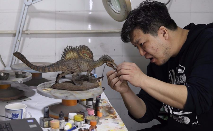 Zhao Chuang crayons gently the colors on a dinosaur model. (Photo/China Daily) In 2006 when he was still in college, Zhao\'s drawing Restoration of Volaticotherium for a research piece was published as the cover of the British Nature magazine.  It was the first time that a Chinese artwork was chosen for the cover of the magazine.  After the publication of the picture on the magazine cover, Zhao won wide recognition from the paleontology community at home and abroad and has become a well-known science artist.