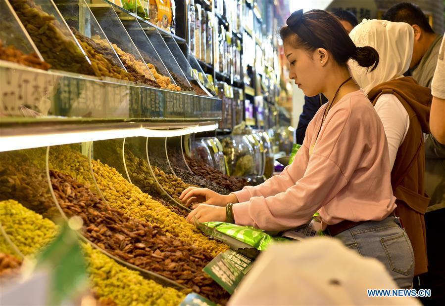 Tourists select dried fruits at the Xinjiang International Grand Bazaar in Urumqi, capital of northwest China\'s Xinjiang Uygur Autonomous Region, April 24, 2017. The Grand Bazaar is a local landmark combining folk culture, ethnic commerce, tourism and entertainment. Food of a particular place is an important symbol of local geographic and cultural characteristics. Food carries history and tradition, leads the tide of trade, strengthens diplomatic relations, disseminates and promotes culture. Food has been serving as connections between people around the world. In ancient times, food such as grapes, pomegranates, walnuts, coriander, cucumbers and sesame seeds were introduced to China along the Silk Road. Nowadays, thanks to the Belt and Road Initiative, red wine, coffee, dried fruits, meat, seafood, and dairy products from foreign countries enter the homes of ordinary people, turning daily meals into feasts with exotic cuisines. (Xinhua/Hu Huhu)