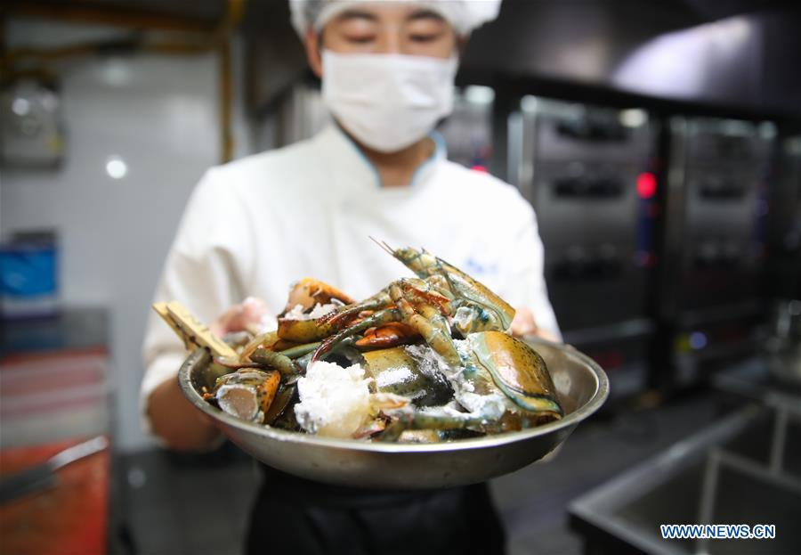 A chef shows American lobsters at one of the Fresh Hema supermarkets in Shanghai, east China, Aug. 8, 2018. It takes 36 hours at the earliest for the fresh lobsters from an aquafarm in Canada to be served on the dining tables of citizens in Shanghai after going through processes of transporting, inspecting, weighing, and selecting. Food of a particular place is an important symbol of local geographic and cultural characteristics. Food carries history and tradition, leads the tide of trade, strengthens diplomatic relations, disseminates and promotes culture. Food has been serving as connections between people around the world. In ancient times, food such as grapes, pomegranates, walnuts, coriander, cucumbers and sesame seeds were introduced to China along the Silk Road. Nowadays, thanks to the Belt and Road Initiative, red wine, coffee, dried fruits, meat, seafood, and dairy products from foreign countries enter the homes of ordinary people, turning daily meals into feasts with exotic cuisines. (Xinhua/Ding Ting)