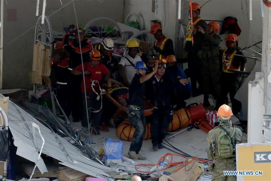 Rescuers carry a survivor out of a collapsed building in Pampanga Province, the Philippines, April 23, 2019. The death toll from the 6.1-magnitude earthquake that struck the Philippines\' main Luzon Island rose to nine, local officials said on Tuesday. (Xinhua/Rouelle Umali)