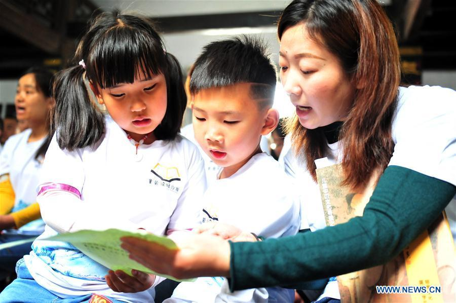 Children and a senior read a list of Chinese classics in Yiling District of Yichang City, central China\'s Hubei Province, April 21, 2019. Various activities have been held across China for the World Book Day, which is celebrated yearly on April 23 to promote reading, publishing and copyright. (Xinhua/Zhang Guorong)