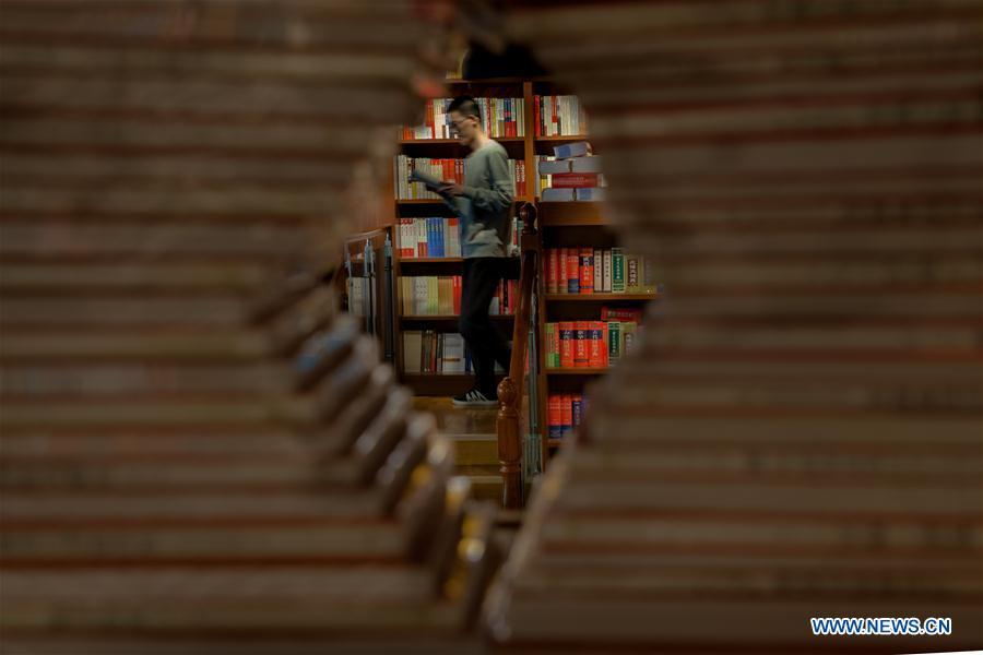 A reader reads a book in a bookstore in Gaoqing County, east China\'s Shandong Province, April 22, 2019. Various activities have been held across China for the World Book Day, which is celebrated yearly on April 23 to promote reading, publishing and copyright. (Xinhua/Zhang Weitang)