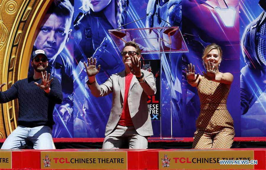 Actor Robert Downey Jr. (C) , Chris Evans (L) and actress Scarlett Johansson show their hands after putting their handprints in cement during print ceremony in the forecourt of the TCL Chinese Theater in Los Angeles, the United States, April 23, 2019. The cast of Marvel Studios \