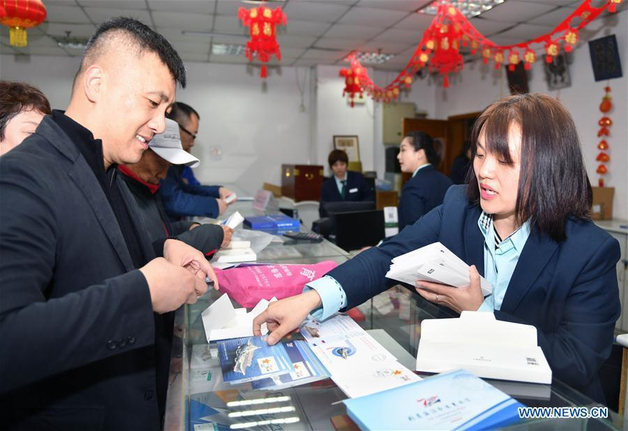 Citizens buy commemorative envelopes at a shop in Qingdao, east China\'s Shandong Province, April 23, 2019. A set of philatelic items were issued on Tuesday to mark the 70th founding anniversary of the Chinese People\'s Liberation Army (PLA) Navy. (Xinhua/Zhu Zheng)
