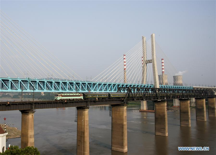 The last train runs on the previous Baishatuo Yangtze River railway bridge in Jiangjin of southwest China\'s Chongqing Municipality, April 23, 2019. The previous Baishatuo Yangtze River railway bridge, completed in 1959, will stop service after April 24. All trains will run on the new double decker steel truss cable stay railway bridge after that day. The new bridge has 4 tracks on the upper deck for passenger trains with a designed speed of 200 kilometers per hour and 2 tracks on the lower deck for cargo trains with the designed speed of 120 kilometers per hour. (Xinhua/Liu Chan)